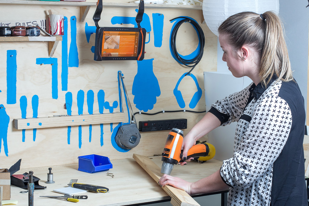 female using drill and tablet for DIY